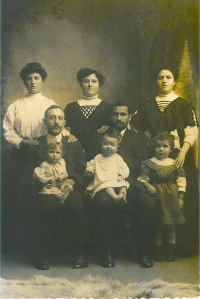 Image: sepia (brown and white) photo of eight people in formal dress of the early part of the 20th Century.  In the back row, three women (standing) in high-collared blouses, all apparently in their 20's or 30's; in the middle row, two men (sitting) wearing suits; the one on the left has a moustache; the one on the right has a full but neat beard.  In the front row, three children.  Two toddlers sit on the men's knees.  One perhaps 4-year-old stands on the right, with one of the women's hands on her shoulder.