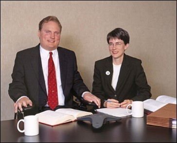 Tim and Amy at a conference table ca. 2000. (Tim is a white man with short blond hair who uses a wheelchair. He is dressed in a suit. Amy is a white woman with short brown hair and glasses. She is sitting in a chair, also wearing a suit. In the foreground, a table posed with law books, a speaker phone, files and mugs.