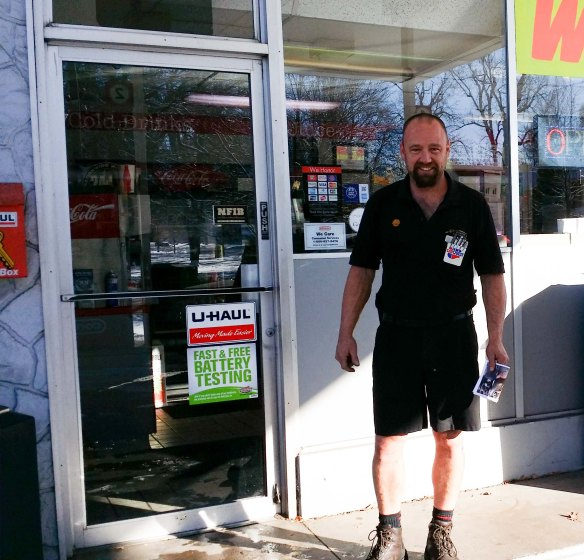 Image:  Man standing in front of a gas station door, wearing shorts and a short-sleeved shirt.  The man is white with brown hair and a goatee.