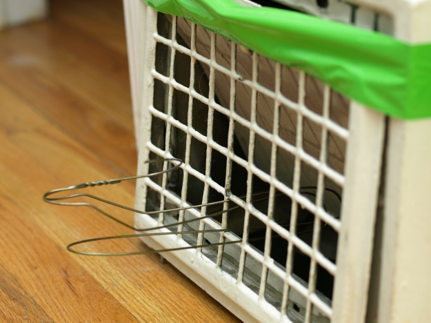 Image:  an old metal heating grate, taped to the wall with green duct tape, held open with a wire coat hanger.