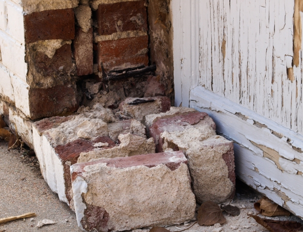 Image:  Close up of 5 or 6 bricks with mortar attached, on the ground next to a brick wall.