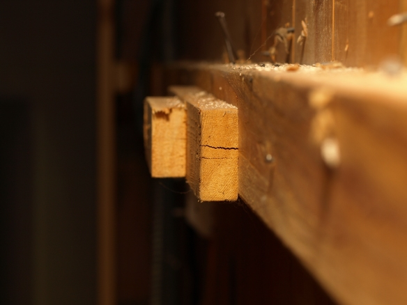Image:  close up of several layers of pieces of wood nailed together - and splitting -- on the side of a wall.