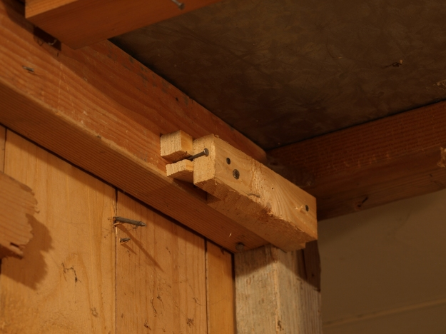 Image:  several layers of pieces of wood nailed together - and splitting -- on the side of a wall.