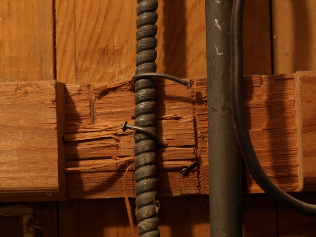 Image:  close up of electrical casing attached by bent nails to hacked up 2x4
