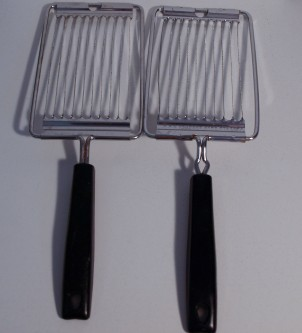 Imate:  Two identical tools consisting of a handle and an approximately two-inch by four-inch set of parallel blades.