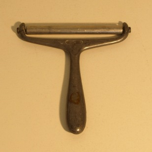 Image: old cheese parer with handle and single blade.