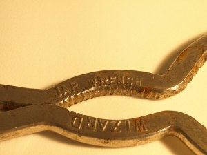 "Image:  close up of old style jar opener showing the words  ""jar wrench wizard."""