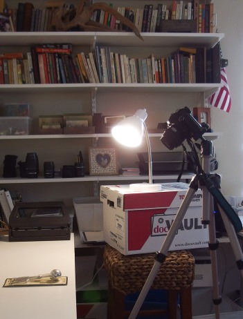 Image:  Camera set up to photograph objects on a table.  Lighting comes from a desk lamp on top of a cardboard box on top of a stool.