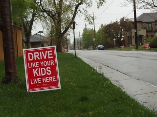 "Image: Red lawn sign with white letters that read ""Drive Like Your Kids Live Here.""  Other lawns in the background have the same sign."