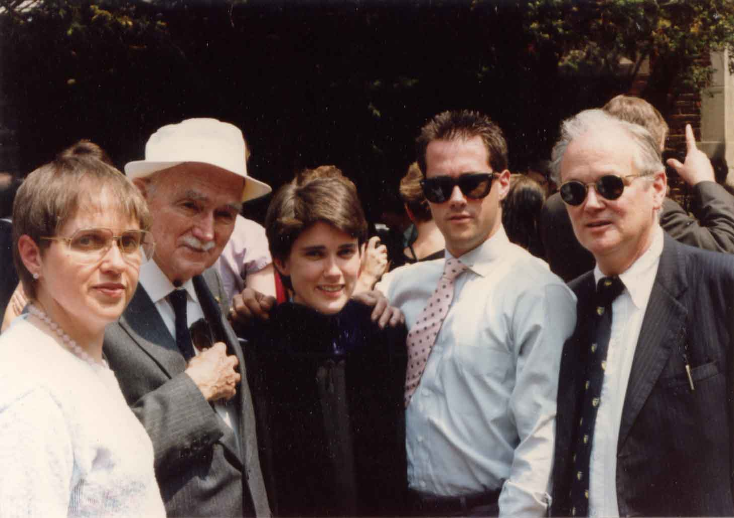 Image: 5 white people posing in front of a building. Mom (brown/gray hair and glasses in a white sweater); older man in suit and white fishing hat; me (short brown hair; graduation gown); younger man in spiked hair with sunglasses in a shirt and tie, and slightly older man in a suit and tie, also with sunglasses.