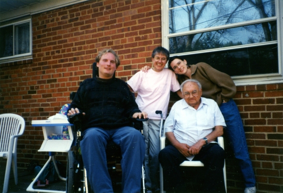 Image: four people, all white, posed on the patio in back of a brick house - man with blond hair in dark sweater using a wheelchair, woman in pink t-shirt, older (balding) man sitting in lawn chair wearing light blue shirt; me with an uncharacteristic pony tail wearing a brown sweatshirt and jeans.