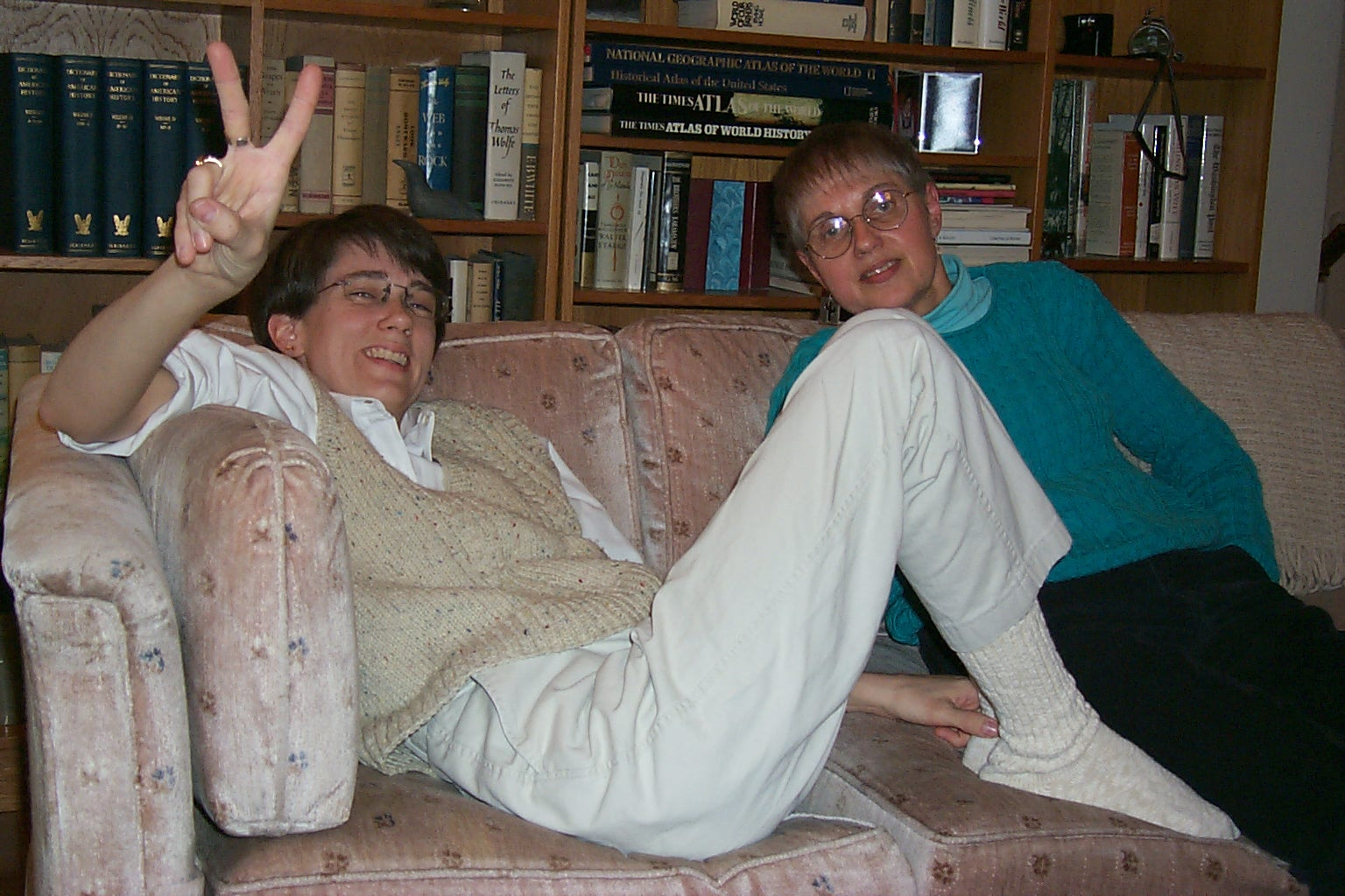Image: two women, both white, sitting on the sofa. Me with short brown hair and glasses wearing a knit vest and khakis; Mom with short brown/gray hair and glasses wearing a green sweater.