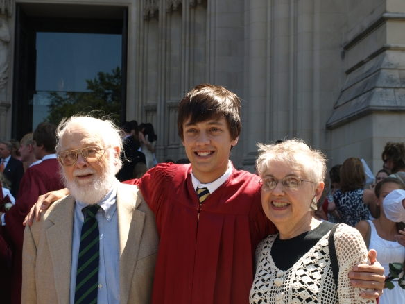 Image: three people in front of a gothic-looking building: an man with white hair and beard in a suit and tie; younger man in a tie and red graduation gown; and Mom in a crocheted shirt with a black shirt underneath.
