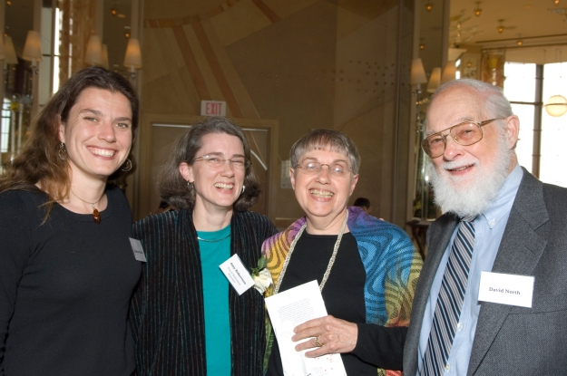 Image: four people, all white: young woman with long brown hair; slightly older woman (me), with salt and pepper hair and a green shirt; Mom in black shirt and patterned shawl, and older man (David) in a suit and tie.