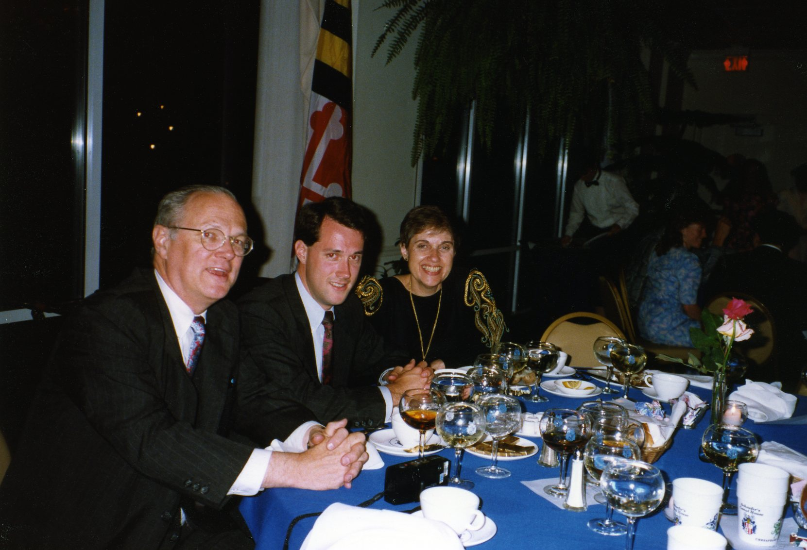 Image: three white people sitting at a restaurant table; man in suit with glasses; younger man also in suit; woman (Mom) in black dress with gold-embroidered sleeves.
