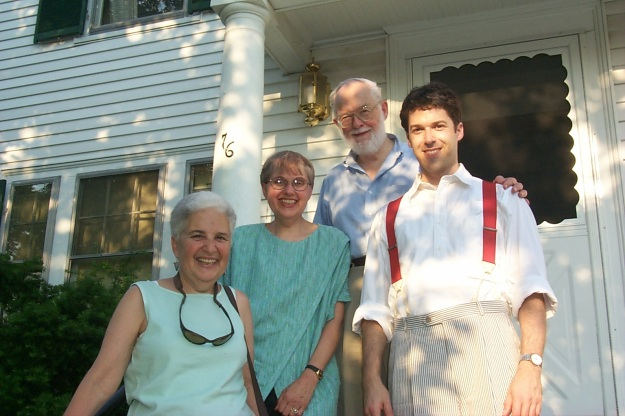 Image: four people, all white, posed in front of a house: woman with gray hair in green t-shirt; woman with brown/gray hair and glasses and green dress; man with white hair an beard in blue shirt; younger man with brown hair in white shirt and striped pants with red suspenders.