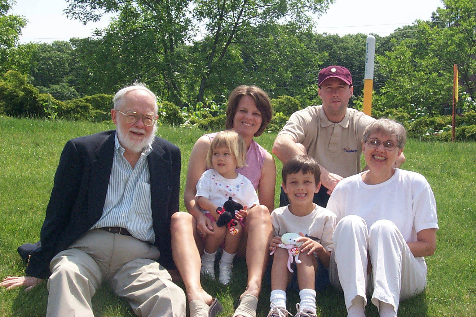 Image: six people, all white posed sitting on a lawn: older man, white hair & beard; young woman in a pink t-shirt holding a toddler with a plush animal in her lap; young boy in t-shirt also with beanie baby toy, man wearing ball cap and beige polo shirt, and mom, in a white t-shirt and khakis.