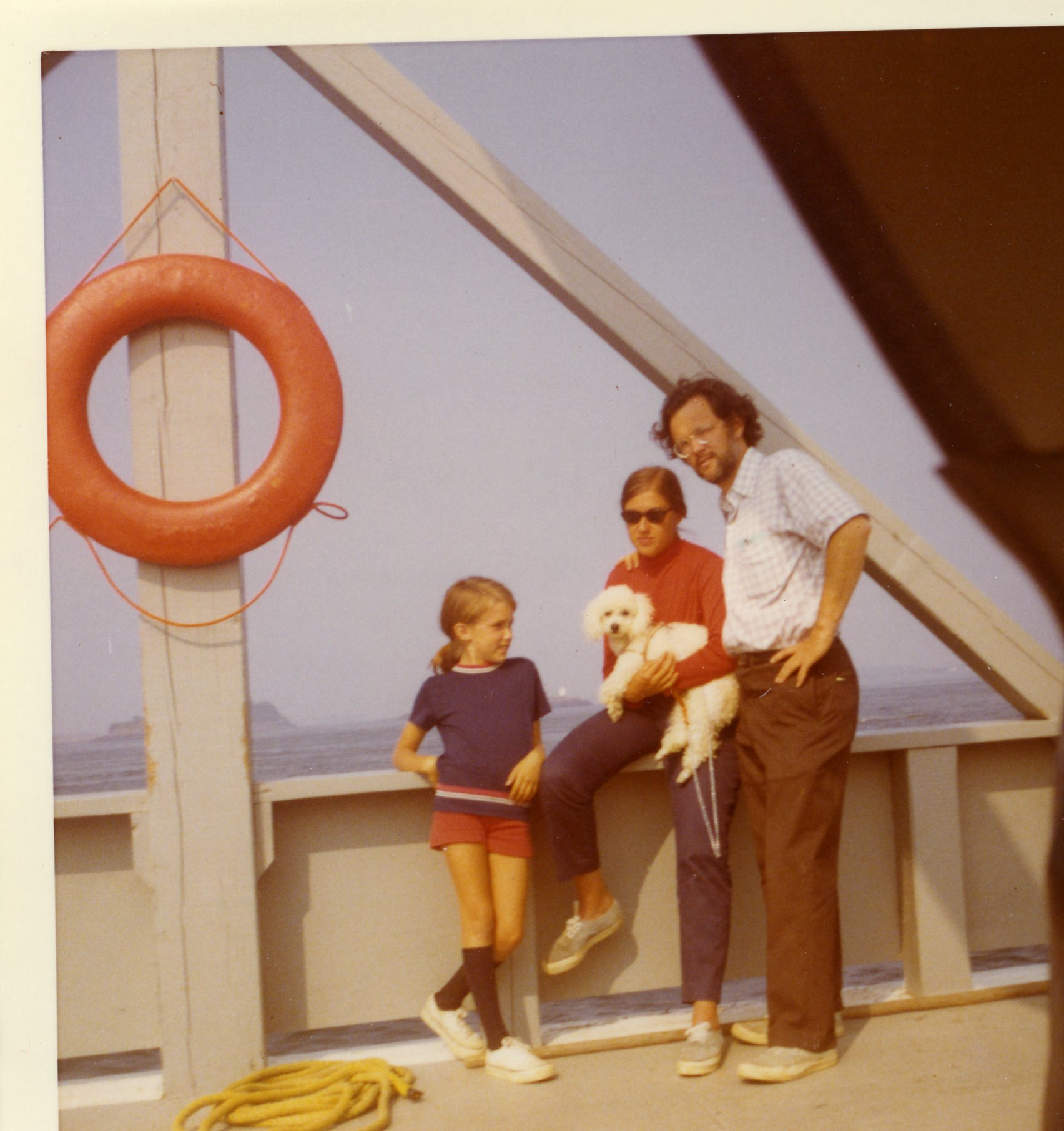 Image: three white people and a dog pose on the side of a boat: girl with ponytail wearing a blue t-shirt and red shorts; woman in red shirt and sunglasses; man with curly brown hair and beard in shortsleeve shirt and brown pants.