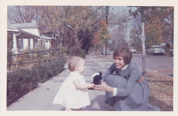 Image: White woman with brown hair in a blue dress squatting down to holdsa toy out to a white toddler in a white dress. They are on the sidewalk in front of a row of houses.