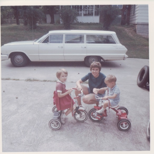 Image: white woman & 2 white kids on tricycles posed on a driveway in front of a white station wagon.