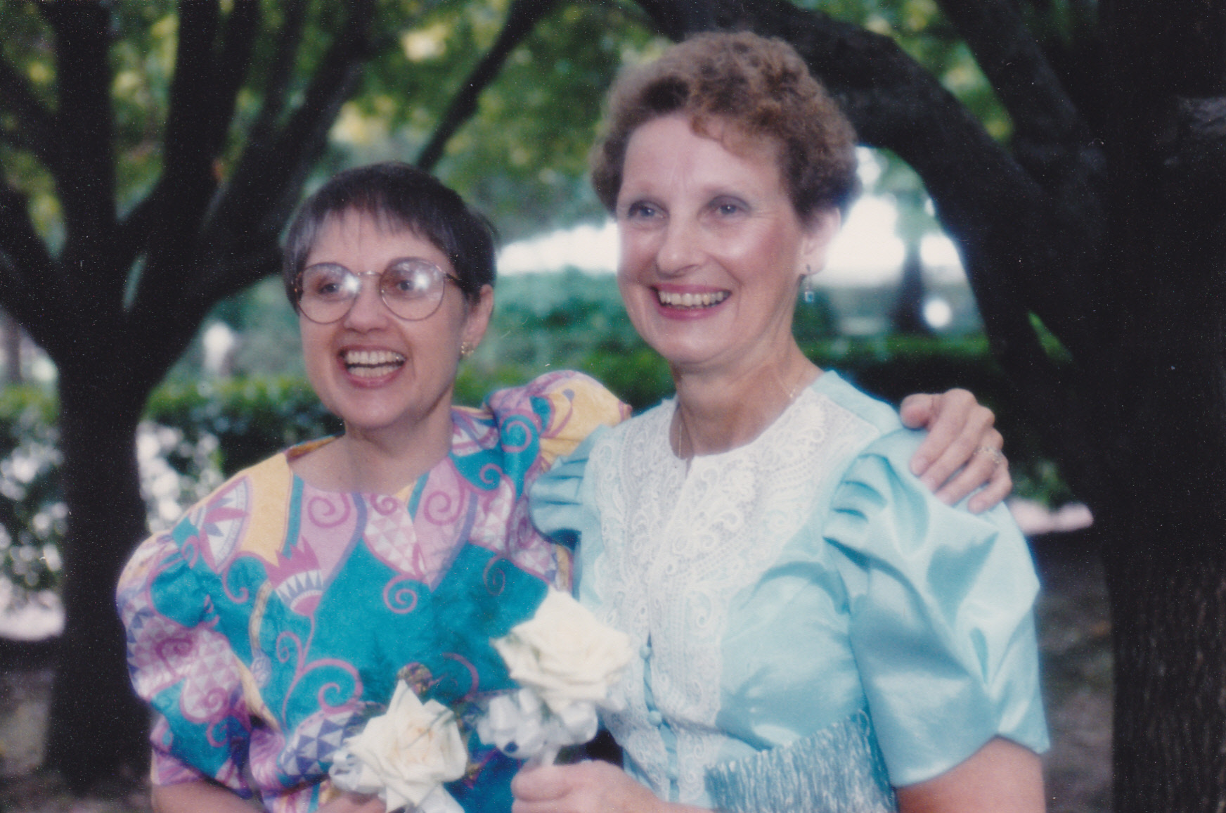 Image: two white women in party dresses, one with straight brown hair and glasses, the other with curly hair; both holding white roses.