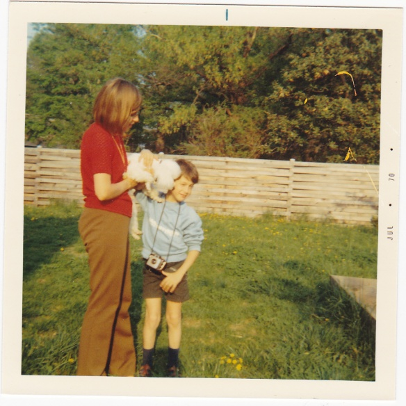 Image: white woman in shortsleeve red shirt holds a small white dog that is licking the face of a small boy in a blue sweatshirt and shorts with a camera around his neck.
