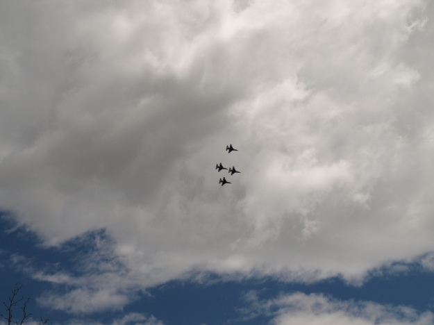 Image: 4 fighter jets flying in formation seen from below with clouds as the background.