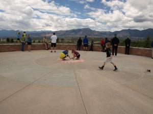 Image: people congregate on a concrete patio area facing the mountains while two young girls draw in chalk on the concrete and a young boy strides toward them.