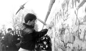 Image:  black & white photo of a man with a pick ax swung back over his shoulder, about to bring it down on a graffiti-filled wall.