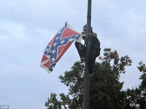 Image: African American woman in climbing gear and helmet, climbing down a flag pole with the Confederate flag in her hands.