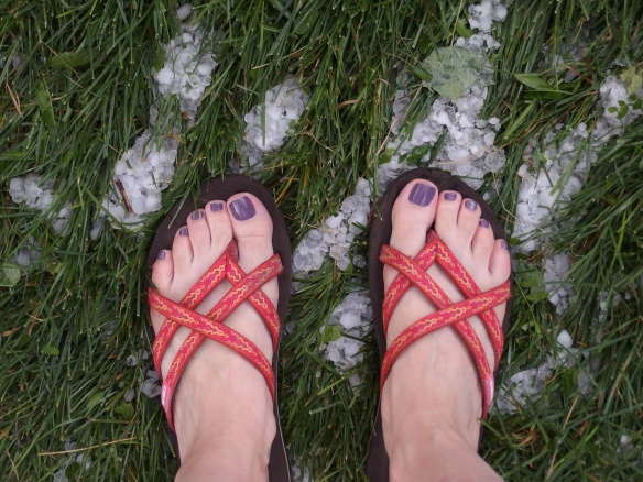 Image: photo of women's feet with purple toenails in flip flops standing on green grass covered with hailstones.