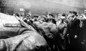 Image:  Black and white photo of men gathered around the head and chest of an enormous statue of Lenin lying prone on the ground.