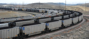 {Image: four parallel coal trains rounding a bend in the track, the front two with coal cars full of coal.}