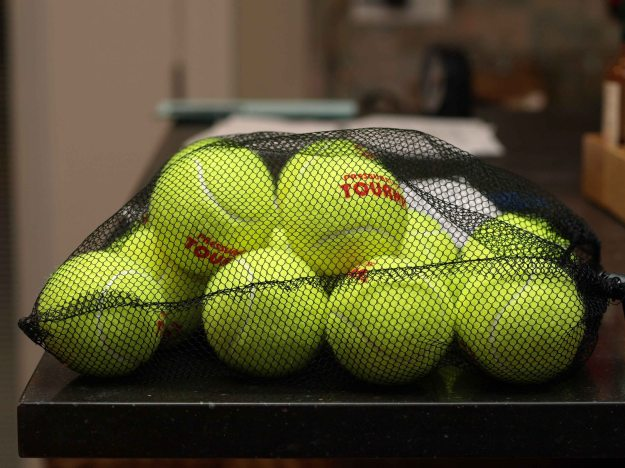 {Image: mesh bag full of tennis balls.}