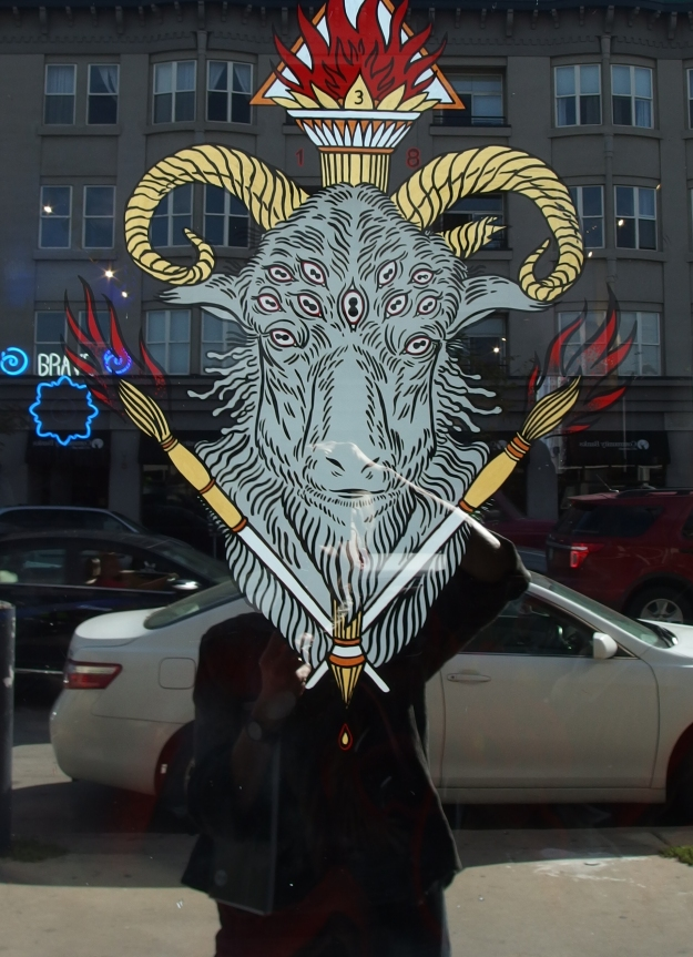 Image: painting on store window of goat-like creature with multiple eyes who appears superimposed on a reflection of the photographer's body.