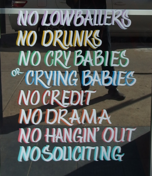 "Image: Store window with painted text that reads, ""No lowballers; no drunks; no crybabies or crying babies; no credit; no drama; no hangin' out; no soliciting."""