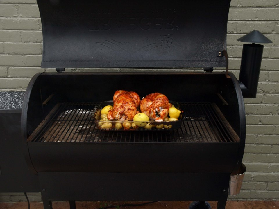 Image: Outdoor grill smoker with a glass baking dish containing potatoes and two whole chickens, spiced with smoked pimento.