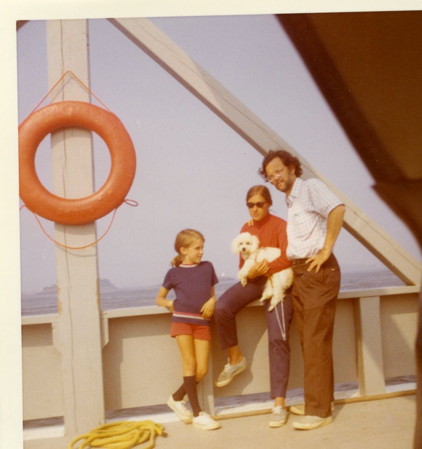 Image: three white people leaning on the side of a ferry boat. The young girl, around 9 years old, is wearing red shorts, a blue shirt and knee socks, the woman (holding a small dog) is wearing blue pants and a red shirt, and the man (with a scruffy beard) is wearing a short-sleeve button-down shirt and brown work pants.