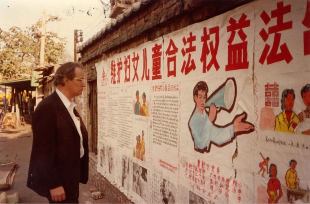 Image:  White man in suit reading wall posters in Chinese.