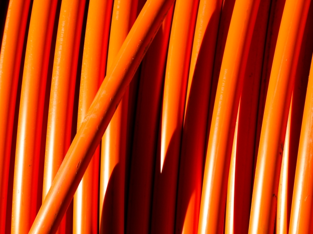 Image:  Close up of bright orange piping arrayed vertically in the photo.