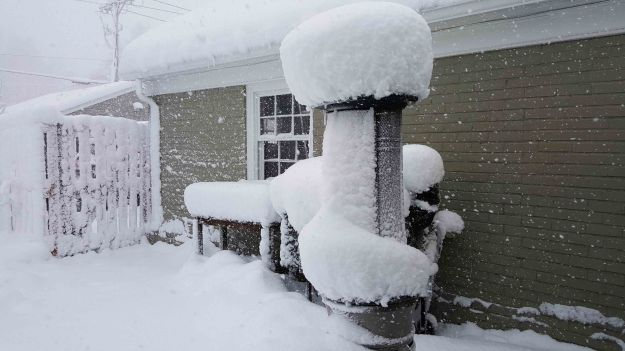 Image: Tall propane heater on a back patio with a large pouf of snow on top.
