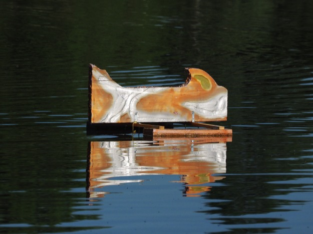 Image: sculpture floating in the lake; appears to be a stylized metal fish.