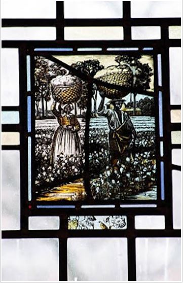 {Image: stained glass window showing a man and woman, both with dark skin, in 19th century clothing, standing in a cotton field, each with a basket of cotton on their head.}