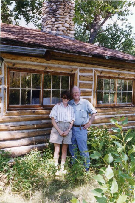 Image: white woman (Amy) in short sleeve shirt and khaki shorts and older white man (Amy's dad) in a short sleeve shirt and blue pants stand in front of log cabin.