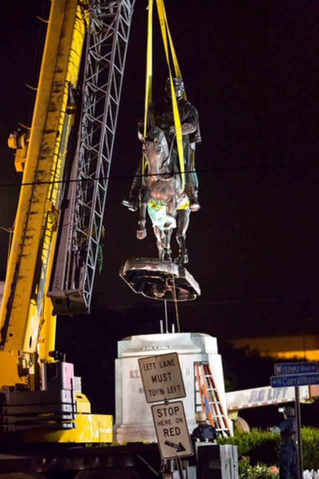 Image: a construction crane lifts a statue of a man on a horse off of its pedestal.