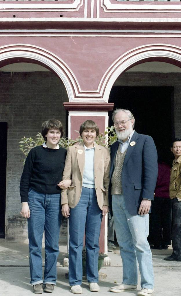 Image: three white people posed in front of a building; me (short brown hair, dark sweater, jeans); Mom (short dark hair, blazer, jeans); David (white hair & beard; blazer, knit vest, jeans).