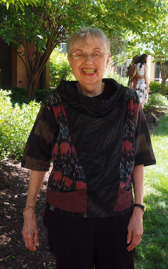 Image: Mom in 2016 standing in front of a leafy background, wearing a patterned black shirt and black pants.