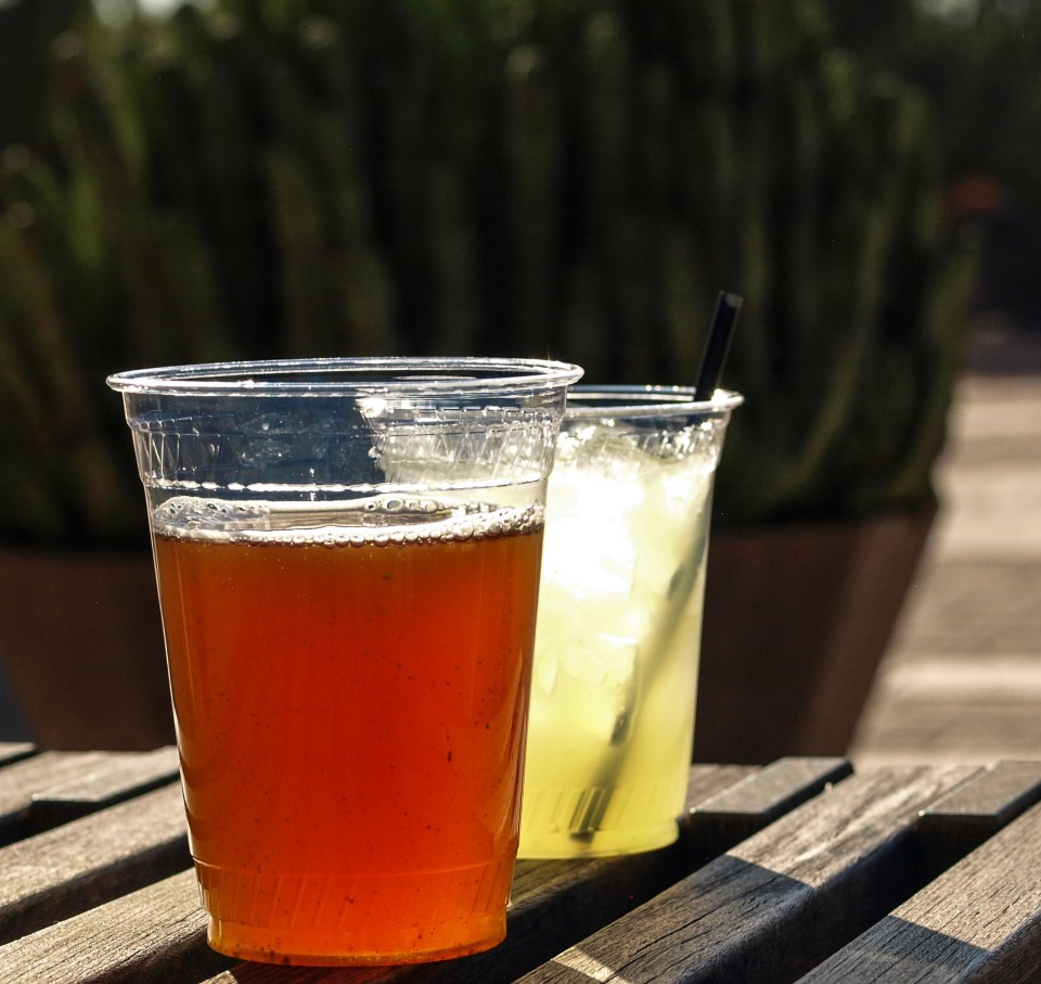 Image: two drinks sitting on a wooden picnic table: a beer without a straw and a margarita with a straw.
