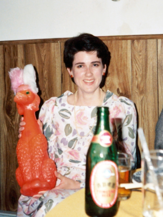 Image: Photo of me at age 28, white woman with short dark hair wearing a flowered dress, holding an orange plastic poodle with pink fuzzy rabbit ears. I'm sitting at a table with a bottle of beer in the foreground.