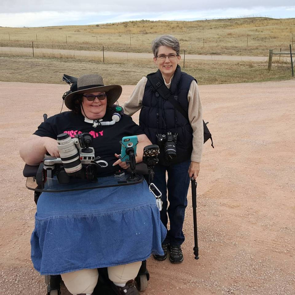 Two white-appearing women with cameras and other photo gear. Carrie, on the left, in a denim skirt and black t-shirt using a wheelchair. Amy, on the right, standing, wearing a beige fleece, vest, and jeans.